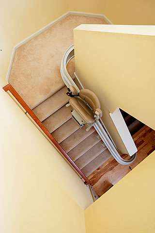 A bird's eye view photo of how the Homeadapt Elite Curve stairlift can be parked part-way up curved angled stairs, then seat, armrests and footrest can be closed up, providing clear access to the stairs.