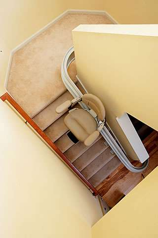 A bird's eye view photo of how the Homeadapt Elite Curve stairlift is traveling part-way up curved angled stairs. The seat, armrests and footrest are set to the open positions.