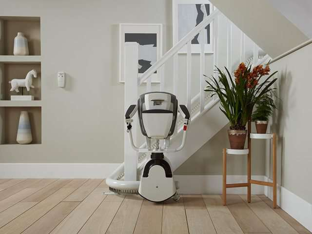 A grey coloured upholstery Flow stair lift parked neatly at the bottom of the stairs around a curve to keep the stairs area as clear as possible. The stairlift chair seat, armrests and footrest are all up, showing how little space the chair takes up when not required.