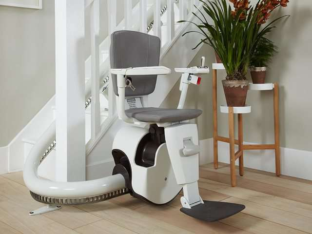 An oblique angle photo of grey coloured Flow stair lift parked at the bottom of the stairs, around the curve to give full free access to the stairs for people who do not need the use of the stairlift. The stairlift chair seat, arm rests and foot rest are all in the down position, so the stairlift is ready for use.