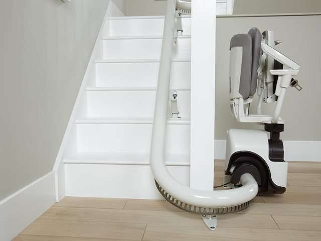 An side angle photo of grey coloured Flow stair lift parked at the bottom of the stairs, around the curve to give full free access to the stairs for people who do not need the use of the stairlift. The stairlift chair seat, arm rests and foot rest are all in the up position to better show how little space the closed-up stairlift chair requires.