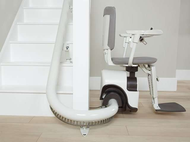 An side angle photo of grey coloured Flow stair lift parked at the bottom of the stairs, around the curve to give full free access to the stairs for people who do not need the use of the stairlift. The stairlift chair seat, arm rests and foot rest are all in the down position so the stair lift is ready for use.