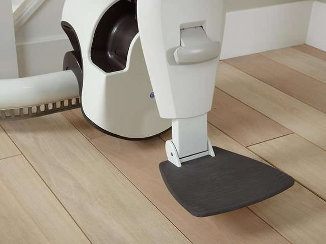A close-up photo of a Flow stair lift footrest in the down position.