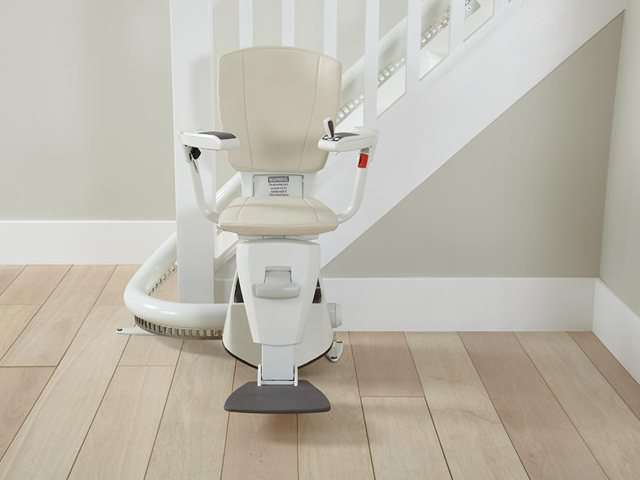 A photo of a light cream coloured upholstery Flow stair lift as it is parked at the bottom of the stairs around the curve, to provide free access to the stairs for people who do not need the use of the stairlift. The stair lift chair seat, armrests, and footrest are all in the down position.
