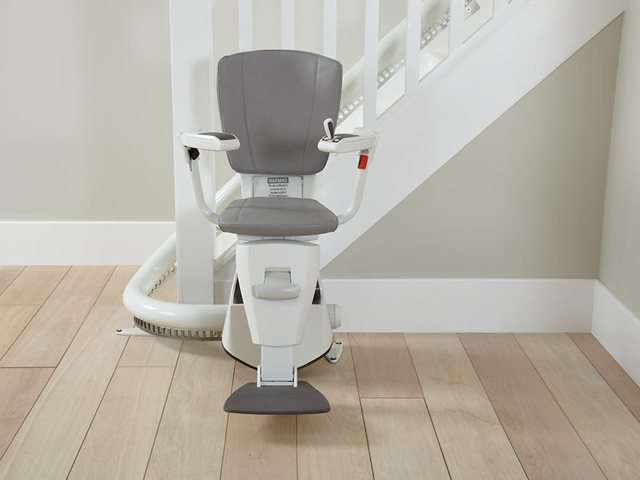 A photo of a grey coloured upholstery Flow stair lift as it is parked at the bottom of the stairs around the curve, to provide free access to the stairs for people who do not need the use of the stairlift. The stair lift chair seat, armrests, and footrest are all in the down position.
