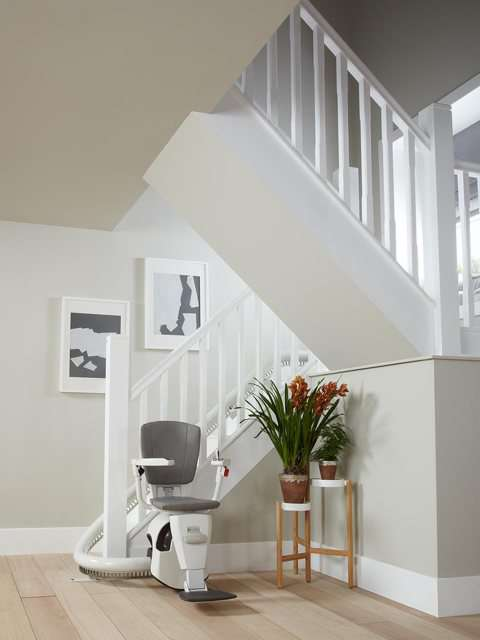 A similar photo to the previous photo, but taken from further back, showing a grey coloured upholstery Flow stair lift parked neatly at the bottom of the stairs around a curve to keep the stairs area as clear as possible. The stairlift chair seat, armrests and footrest are all down, so the stairlift is ready for use.