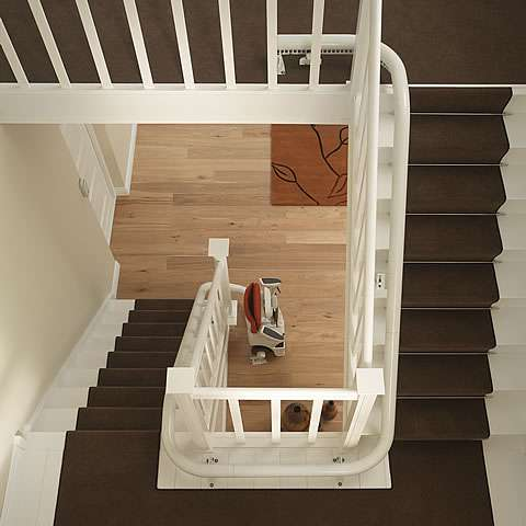 Another bird's eye photo of stairs with multiple curves, bends, and angles, with a red coloured upholstery Flow stair lift installed, clearly illustrating the graceful and space-saving way the stairlift rail follows the bends and curves of the stairs, allow plenty of free access for people who do not require use of the stair lift.