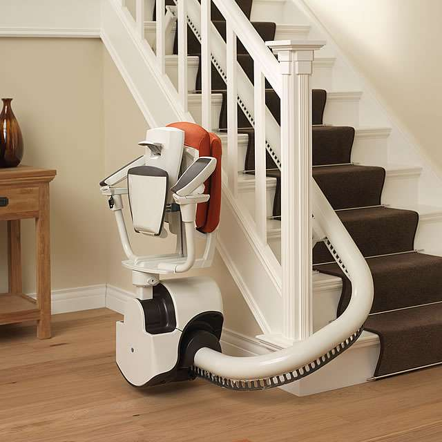 A red colour upholstery Flow stair lift chair parked at the bottom of the stairs, conveniently around another curve to allow full free access to the stairs. The stair lift chair has the seat, arm rests and footrest all in the up position to minimise space used and to help prevent anyone tripping over the stair lift.
