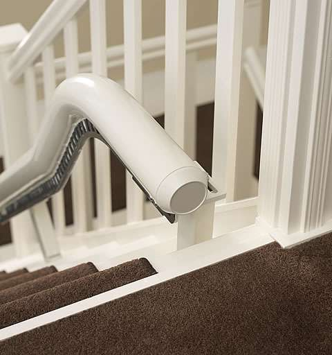 A photo showing how the stair lift rail at the top of the stairs curves up and then and fits neatly to the floor near the top of the stairs.