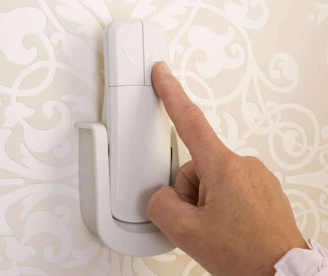 Close-up photo of female user's finger touching a button on the wall-mounted remote control of Homeglide stair lift for straight stairs.