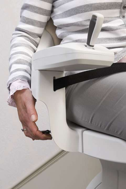 Close-up photo of female user riding on cream-coloured Homeglide stair lift adjusts the swivel lever while traveling down straight stairs.