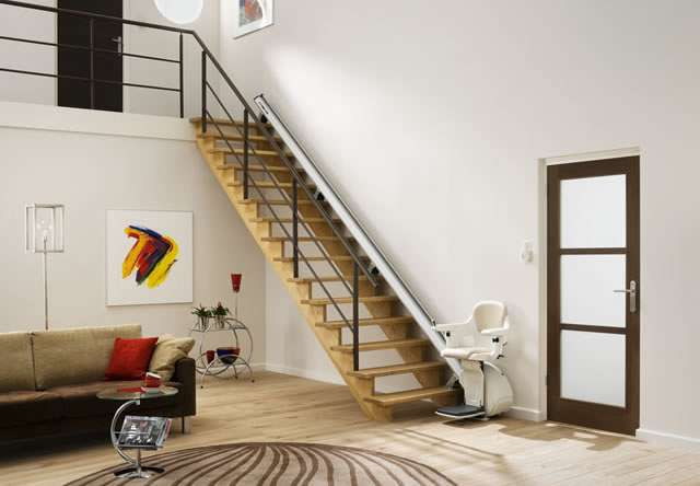 Photo from another angle of cream-coloured Homeglide stair lift with seat, arm rests and foot rest in down position, parked at the bottom of straight stairs.
