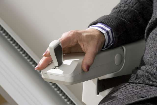 Close-up photo of male user operating arm rest joystick control of cream-coloured Homeglide stair lift while traveling down straight stairs.