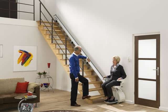 Male user standing near female user seated on cream coloured upholstery Homeglide stair lift situated at the bottom of straight stairs.