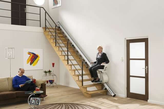 Female user either going up or down straight stairs on cream-coloured Homeglide stair lift, currently near the bottom of the stairs. Male user seated close by on sofa reading a booklet.