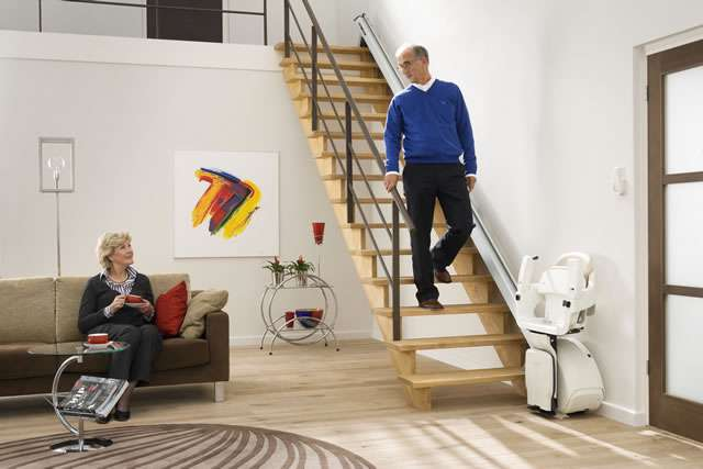 Cream coloured Homeglide stair lift parked at bottom of stairs with arm rests, seat, and footrest in the up position. Male user walking down straight stairs passing in the gap created by the conveniently closed-up stairlift. Female user seated on sofa close by.