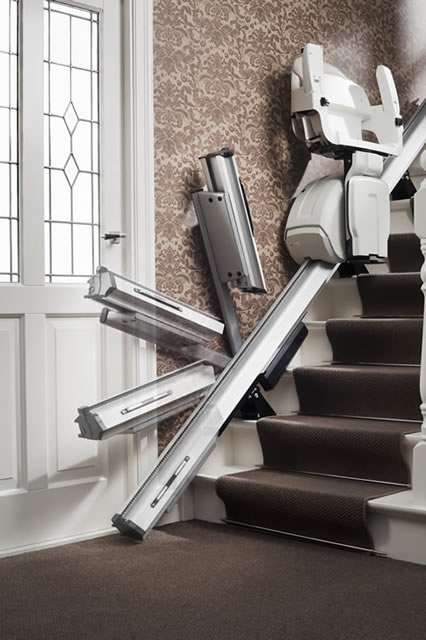 A time-lapse mix photo of the bottom of stairs area of the Homeglide stairlift, focusing on how the end of the retractable stairlift rail safely and conveniently retracts back above the main stair lift rail, to provide clear, safe access to a door.