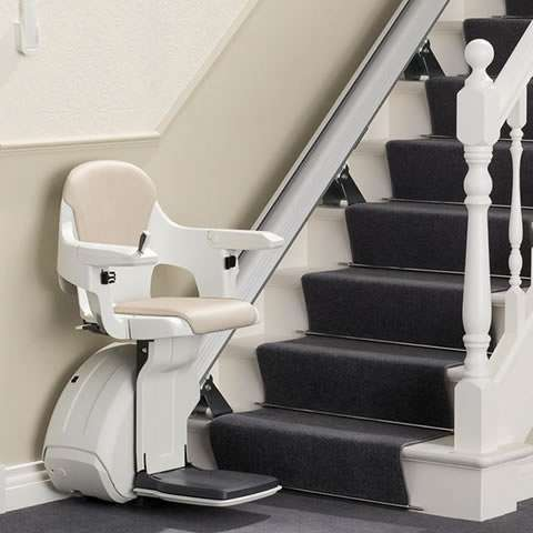 A cream-coloured Homeglide stairlift parked at the bottom of the stairs, with armrest, seat, and footrest all in the down position, ready for use.