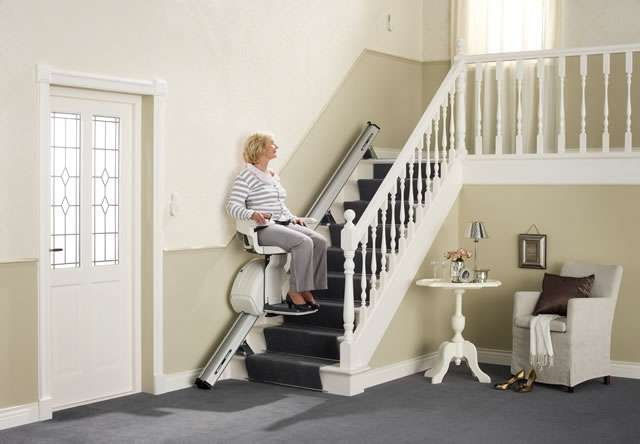 Female user sitting on cream-coloured Homeglide stair lift going up straight stairs.