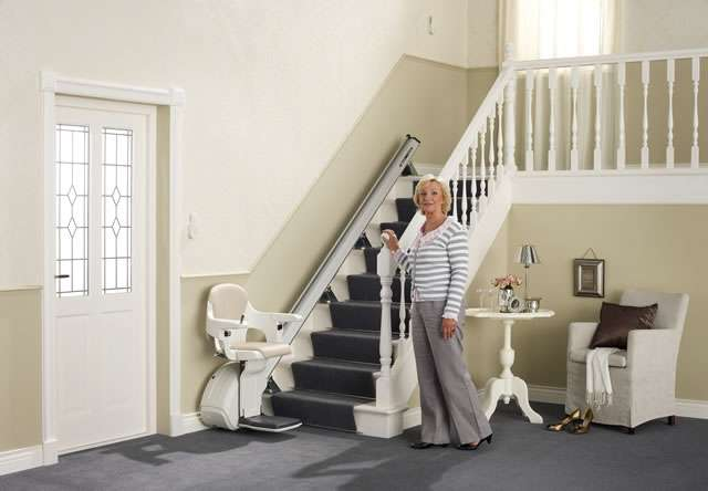 Female user standing near cream-coloured Homeglide stair lift parked at the bottom of straight stairs. Stairlift seat, armrests and footrest all in the down position, ready for user to sit on the stair lift.