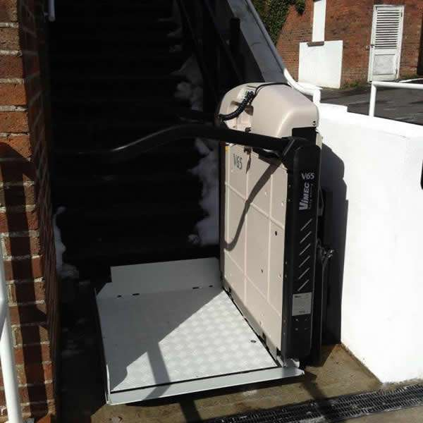 Vimec incline platform lift installation at the bottom of the external steps, from yet another different angle, shows the Vimec incline platform lift in the lowered position to provide easy access for a wheelchair user to navigate on to the platform ready to be transported up the external steps. Plus, also shows the full-surround protection arms