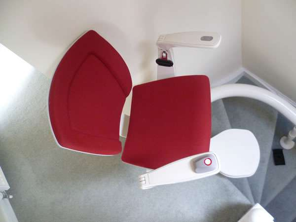 Otolift stairlift installation, red upholstery, stair lift on the bend of curved stairs