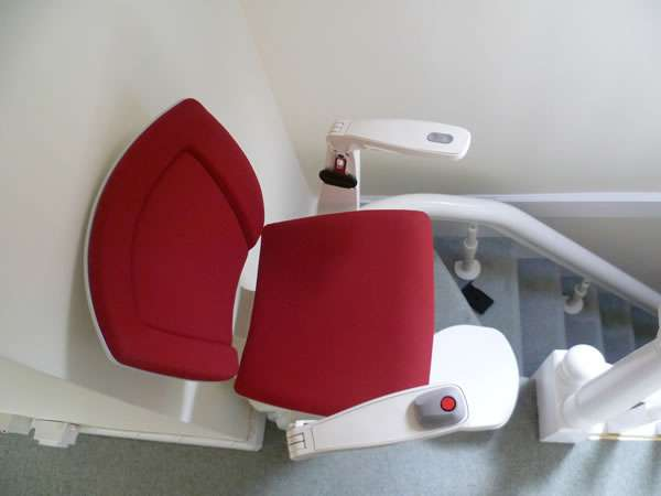 Otolift stairlift installation, red upholstery, bird's eye view of stair lift on the bend of curved stairs