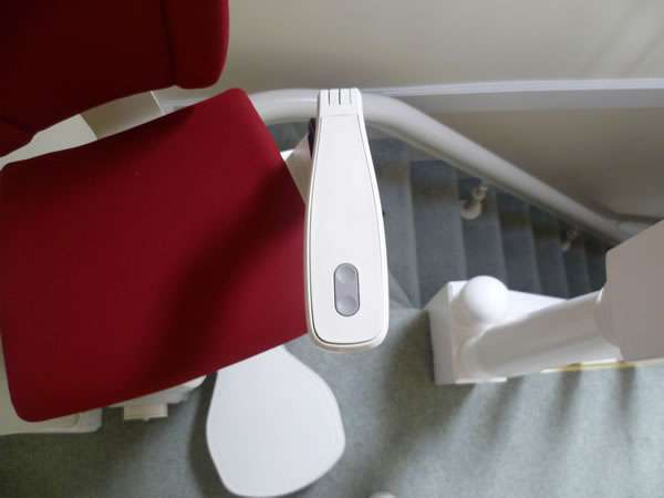 Otolift stairlift installation, red upholstery, stair lift at the top of curved stairs facing the landing. Close-up view of stair lift other arm rest control buttons
