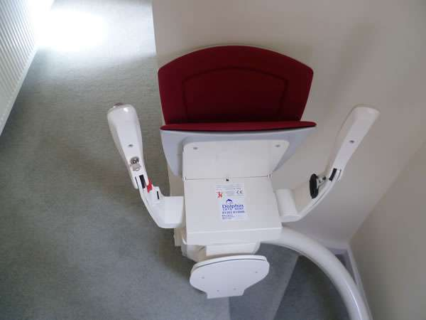 Otolift stairlift installation, red upholstery, stair lift at the top of curved stairs facing the landing, with seat, arm rests and foot rest all in the folded up position, allowing easy access to the stairs for people who do not need use of the stairlift