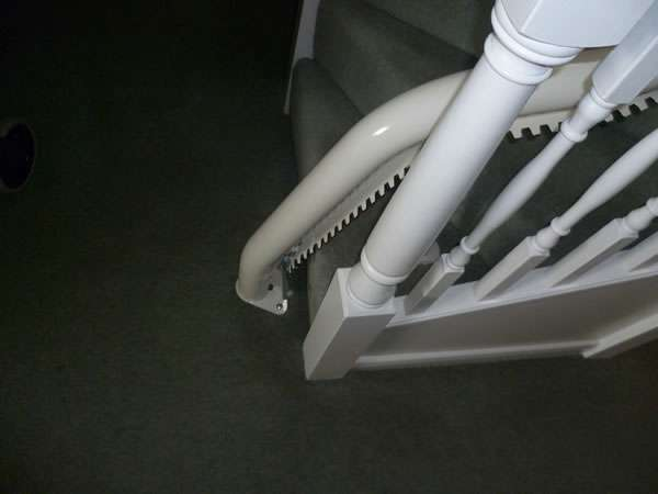 Otolift stairlift installation, red upholstery, showing how the stair lift rail installs on to the floor at the bottom of the stairs
