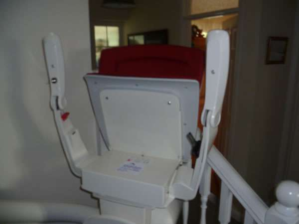 Otolift stairlift installation, red upholstery, with stair lift parked near the bottom of the stairs with seat, arm rests, and foot rest all folded in the up position to allow easier access to the stairs for people who do not need to use the stairlift