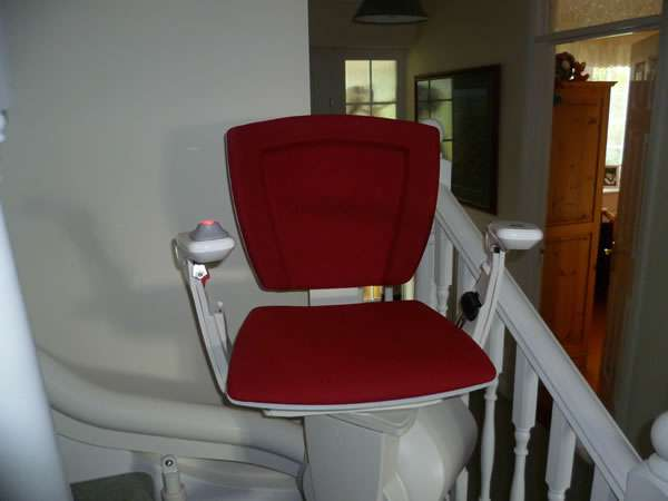 Otolift stairlift installation, red upholstery, showing another angle with stair lift parked near the bottom of the stairs with seat, arm rests, and foot rest all opened out in the down position