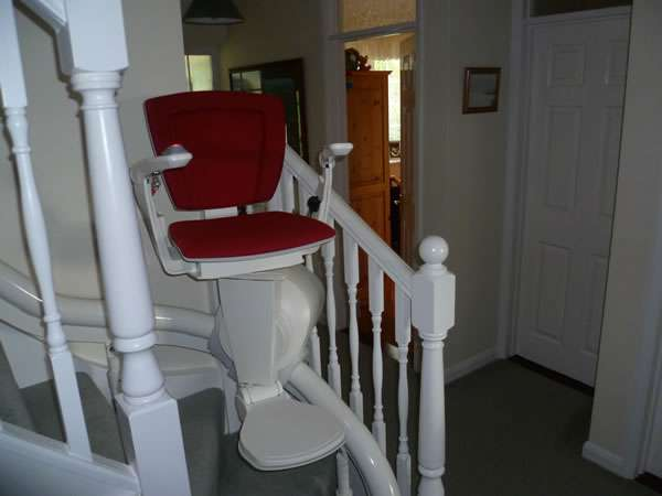Otolift stairlift installation, red upholstery, showing the stair lift situated at the first curve of the stairs, near the bottom of the stairs with seat, arm rests, and foot rest all opened out in the down position