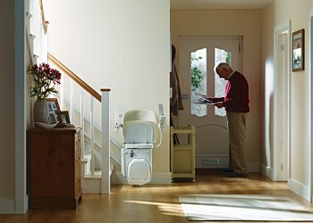 Stannah Siena stair lift for curved stairs. Seat, arm rests, and foot rest can be folded away.