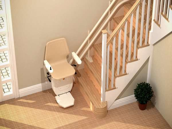 Bird's eye view of beige Dolphin Infinity stairlift parked at the bottom of the stairs, with seat, arm rests and foot rest all in the down position.