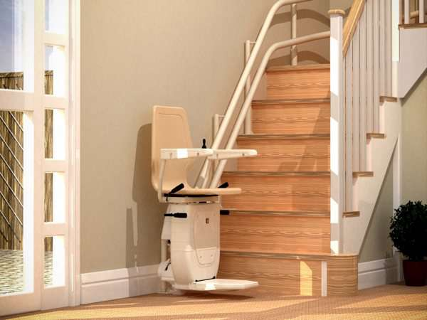Near side view of beige Dolphin Infinity stairlift parked at the bottom of the stairs, with seat, arm rests and foot rest all in the down position.
