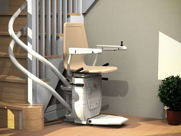 Beige Dolphin Infinity stairlift parked at the bottom of curved stairs, with seat, arm rests and foot rest all in the down position. Chairlift design allows stairlift to be positioned so that it does not obstruct access to the stairs for people who do not require use of the stair lift.