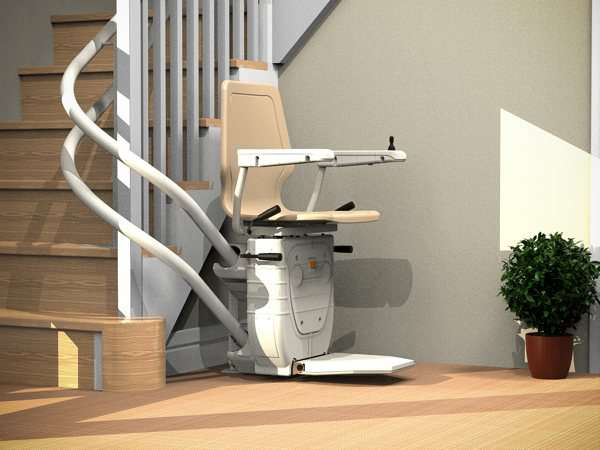 Near side view of beige Dolphin Infinity stairlift parked at the bottom of curved stairs, showing that the stairs are not obstructed.