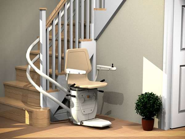 Angled view of beige Dolphin Infinity stairlift parked at the bottom of curved stairs, showing that the stairs are not obstructed.