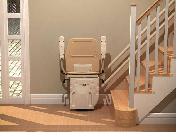 Direct front view of beige Dolphin Infinity stairlift parked at the bottom of straight stairs, with seat, armrests, and footrest in up position, allowing good access to the stairs for people who do not require use of the stair lift.