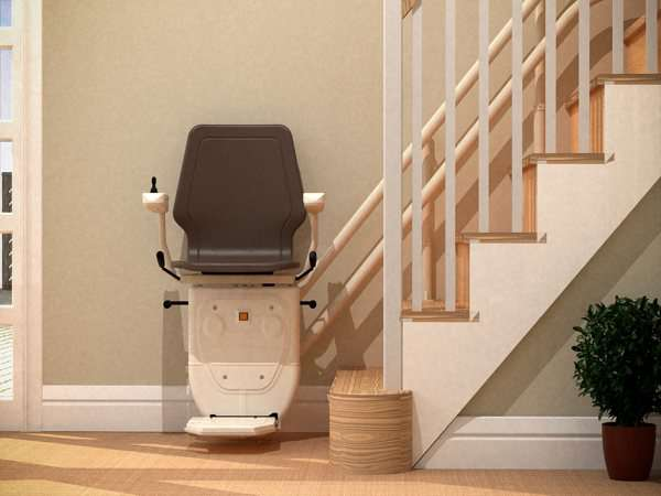 Direct front view of brown Dolphin Infinity stair lift, parked at the bottom of stairs, with seat, arm rests and footrest in the down position.