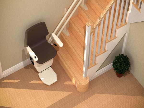 Bird's eye angled view of brown Dolphin Infinity stair lift, parked at the bottom of stairs, with seat, arm rests and footrest in the down position.