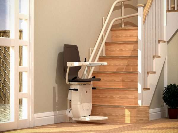 Angled side view of brown Dolphin Infinity stair lift, parked at the bottom of stairs, with seat, arm rests and footrest in the down position.