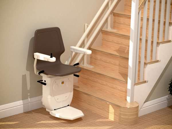 Closer higher angled view of brown Dolphin Infinity stair lift, parked at the bottom of stairs, with seat, arm rests and footrest in the down position.