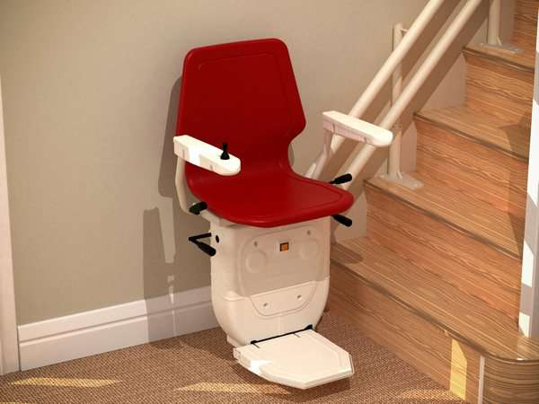 Red Dolphin Infinity stair lift parked at bottom of stairs with seat, arm rests and foot rest in the down position.