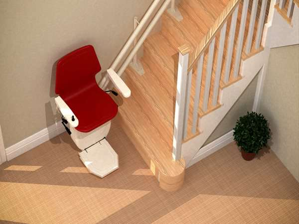 Bird's eye view angled red Dolphin Infinity stair lift parked at bottom of stairs with seat, arm rests and foot rest in the down position.