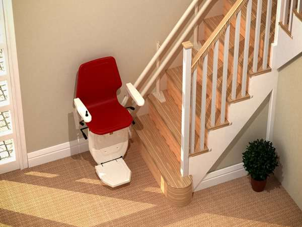 Higher angled view of red Dolphin Infinity stair lift parked at bottom of stairs with seat, arm rests and foot rest in the down position.