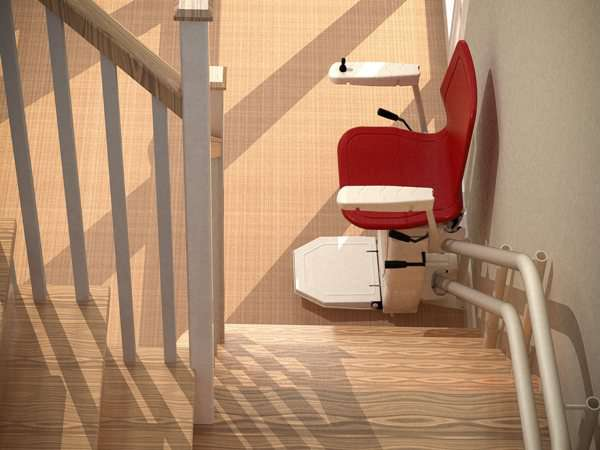 Looking down the stairs, red Dolphin Infinity stair lift parked at bottom of stairs with seat, arm rests and foot rest in the down position.