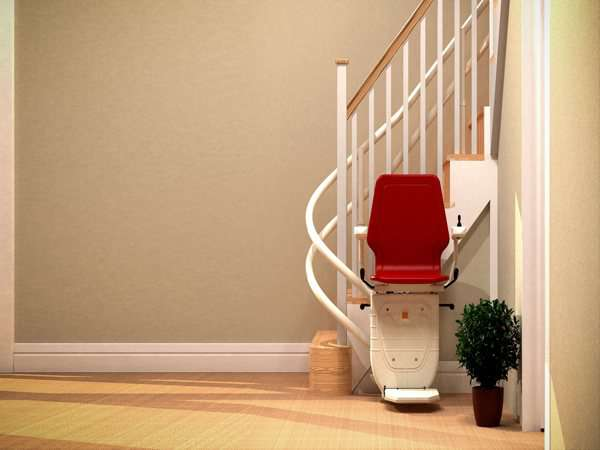 Front view of red Dolphin Infinity stair lift parked at bottom of curved stairs with seat, arm rests and foot rest in the down position, showing how the stair lift is parked around the curve, providing easy access to the stairs for people who do not need the stairlift.