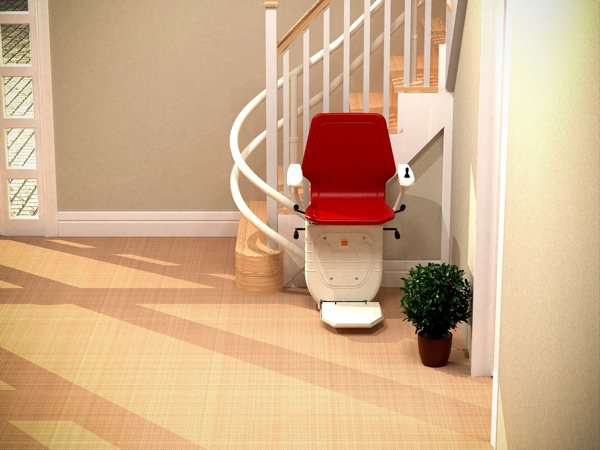 Further back bird's eye angled view of red Dolphin Infinity stair lift parked at bottom of curved stairs with seat, arm rests and foot rest in the down position, showing how the stair lift is parked around the curve, providing easy access to the stairs for people who do not need the stairlift.